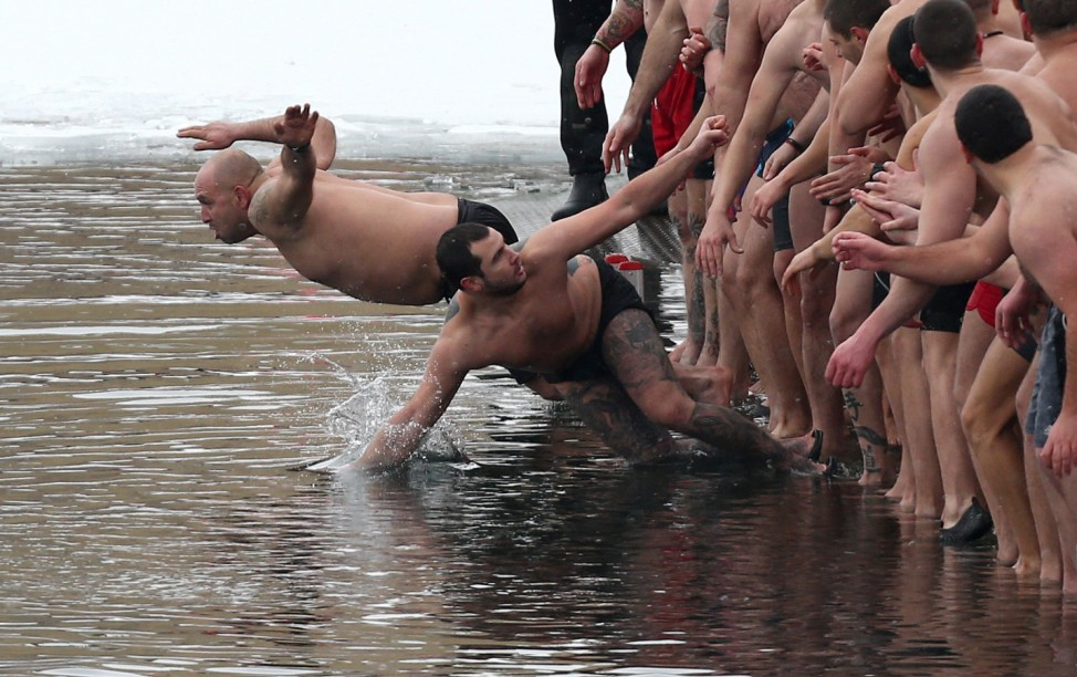 Men jump in the waters of a lake to catch a wooden crucifix during a celebration of Epiphany Day in Sofia