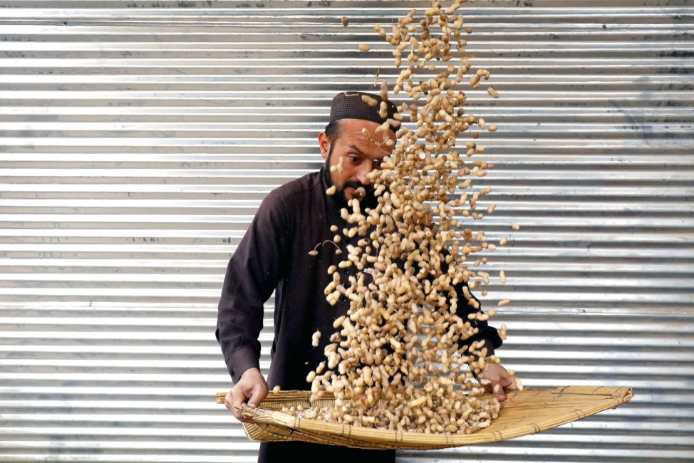 Man cleans peanuts for sale outside a shop in Peshawar,