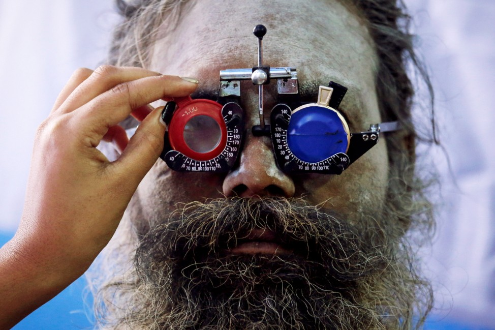 A Sadhu or a Hindu holy man gets his eyes tested at a free eye-care camp at a makeshift shelter before heading for an annual trip to Sagar Island for the one-day festival of 'Makar Sankranti', in Kolkata