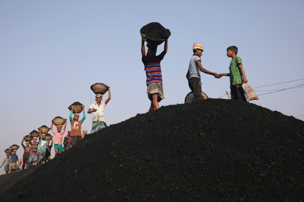 Coal workers are seen at a market as they unload a ferry in Dhaka