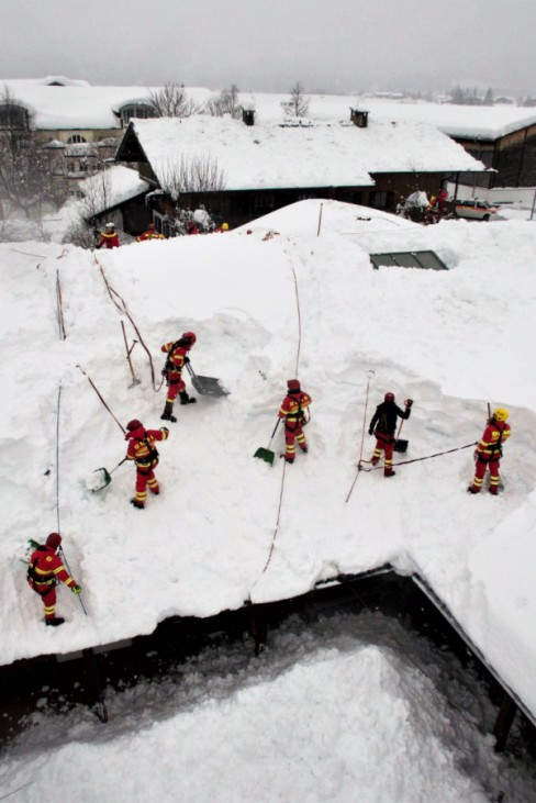 Schleching: Helfer der DLRG-Bayern räumen die Schneemassen von einem Hausdach.