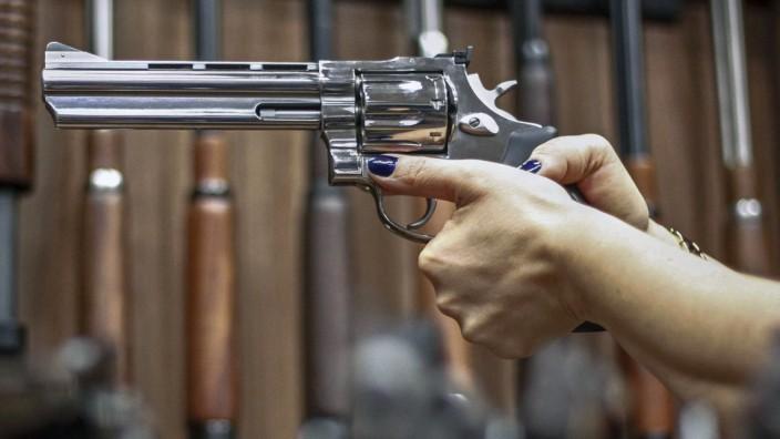 Femizide in Brasilien: Eine Frau zielt mit einem Revolver in einem Waffenladen in São Paulo.