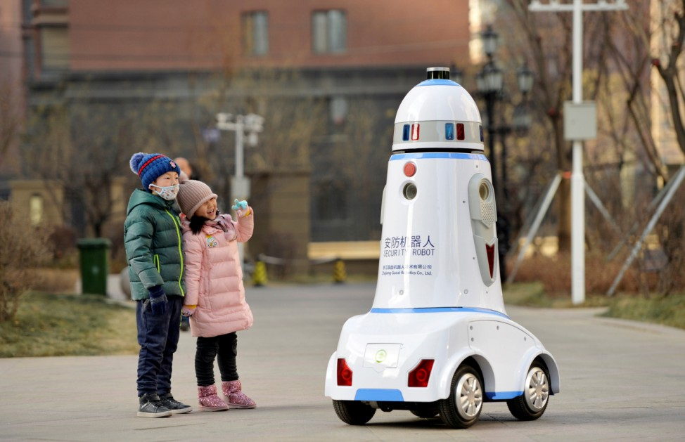Children react next to a security robot patrolling inside a residential compound in Hohhot