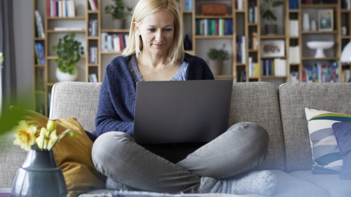 Woman at home sitting on couch using laptop model released Symbolfoto property released PUBLICATIONx