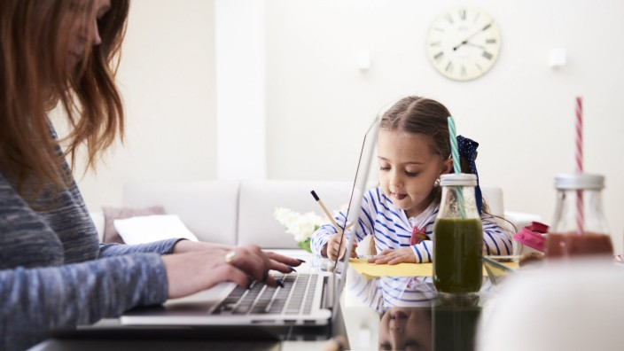 Little girl drawing with pencil at table beside her mother typing on keyboard of laptop model releas