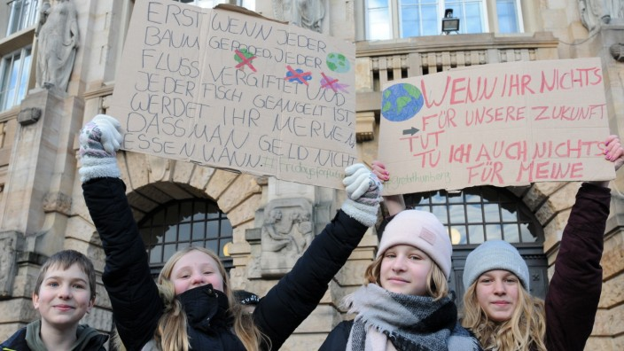 Germany, Freiburg: Thousands of schoolchildren hold placards and chant slogans during a protest demonstration against government's inaction on climate change
