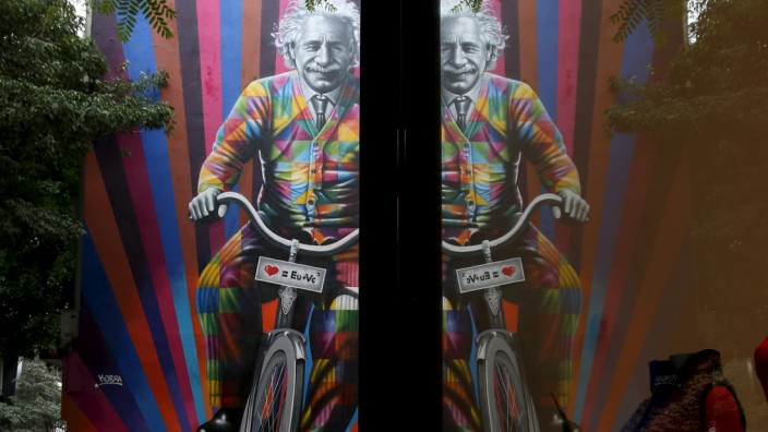 People walk past a mural of Albert Einstein riding a bicycle in Sao Paulo