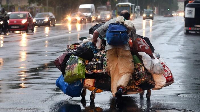 Bilder des Tages Obdachloser versucht sein Hab und Gut vor dem Starkregen in Sicherheit zu bringen B