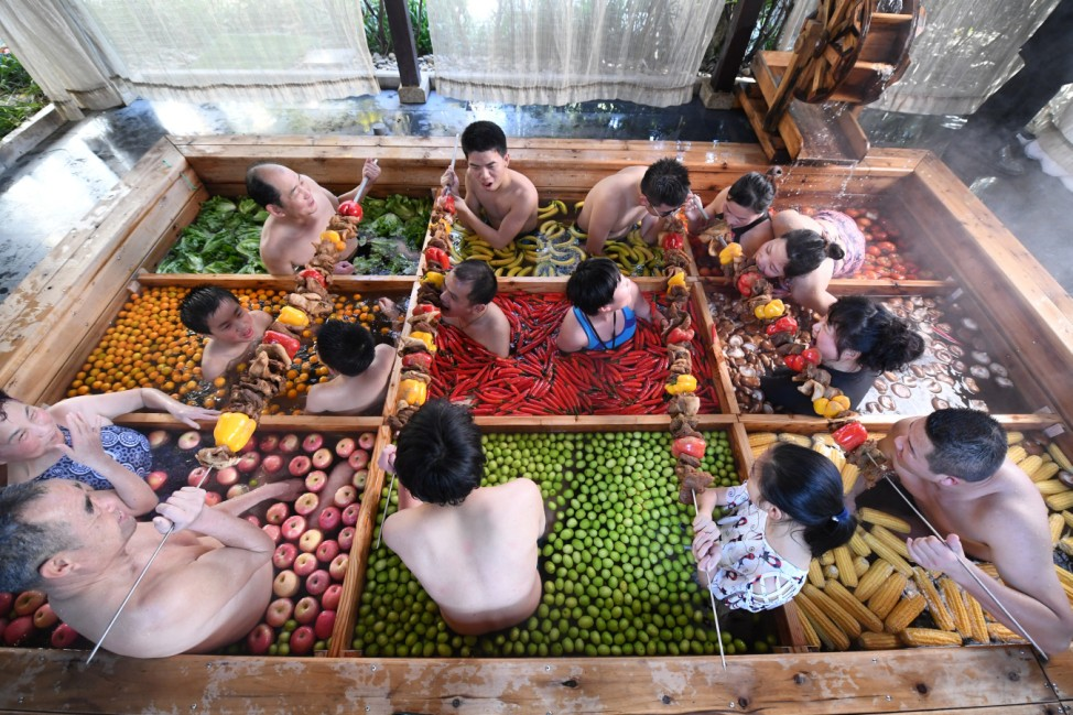 People enjoy a barbecue as they bath in a hotpot-shaped hot spring filled with fruits and vegetables, at hotel in Hangzhou