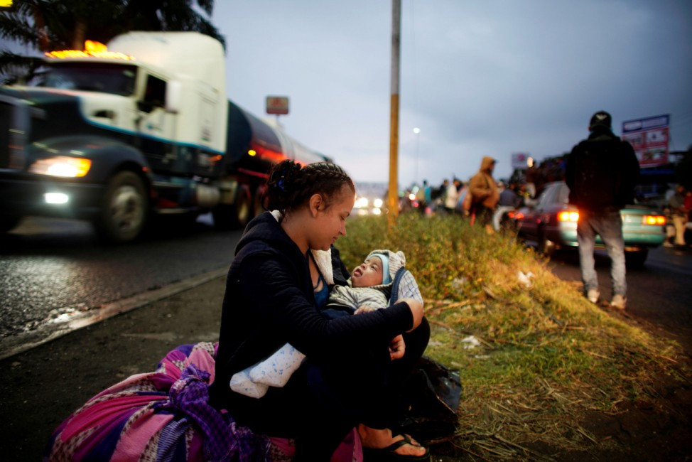 Migrant Marely Villatoro, 20, from Honduras, plays with her 4 months-old child as she waits for a lift during their journey towards the United States, in Tierra Blanca, Mexico