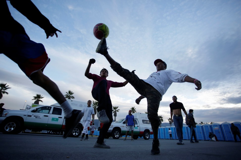 Migrants play soccer in a provisional shelter during their journey towards the United States, in Saltillo, Mexico