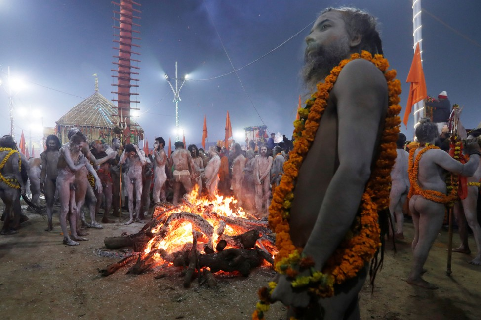 Naga Sadhus or Hindu holy men stands next to a bonfire before a procession at 'Kumbh Mela' or the Pitcher Festival, previously known as Allahabad, in Prayagraj