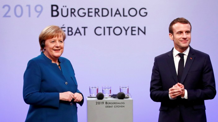 FILE PHOTO: German Chancellor Angela Merkel and French President Emmanuel Macron attend a discussion with citizens, in Aachen