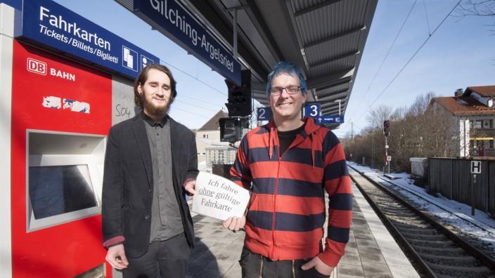 """MVV: """"Erschleichen von Leistungen"""", heißt das Delikt, doch Manuel Erhardt (links) weist auf einem Schild darauf hin, dass er ohne gültige Fahrkarte den Zug benutzt. Vor Gericht begleitet ihn Andreas Schachtner."""
