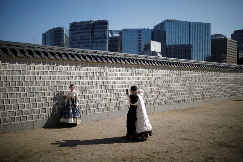 A tourist wearing Korean traditional costume Hanbok poses for photographs at Gyeongbok Palace in central Seoul