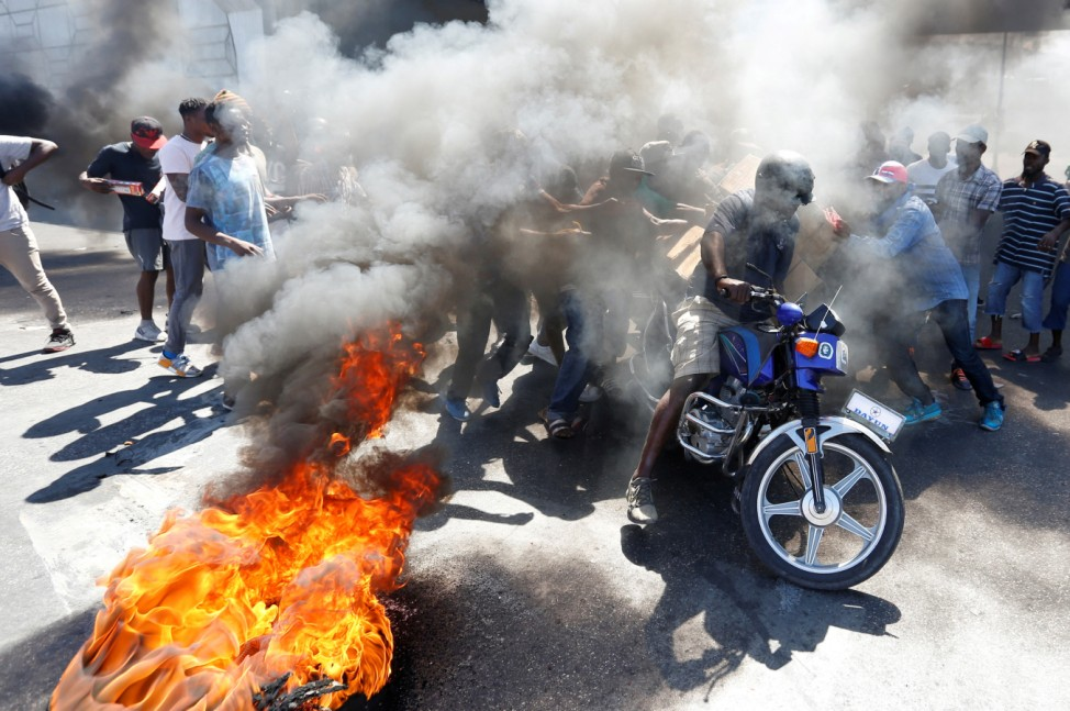 Protesters loot boxes from a biker during a protest against the government in the streets of Port-au-Prince