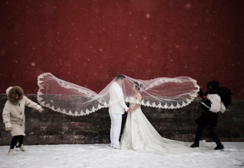Couple poses for a wedding photo shoot amid snowfall at the Imperial Ancestral Temple in Beijing