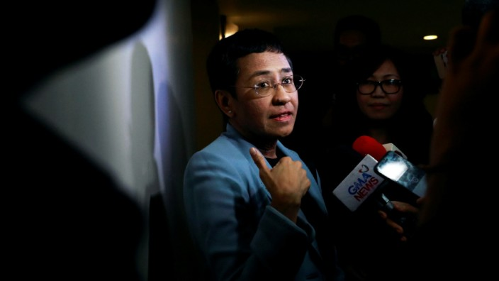 Maria Ressa, an executive of online news platform Rappler, speaks to the media after being served an arrest warrant in Rappler's office in Pasig City