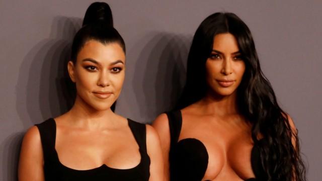 Kim Kardashian and her sister Kourtney Kardashian pose on the red carpet for the amfAR gala in New York