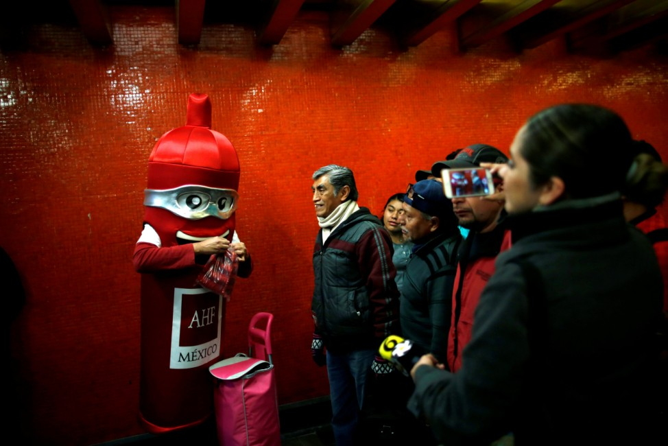 A man wearing a costume, representing a condom, is seen at a metro station giving free condoms on the International Condoms Day, celebrated a day before Valentine Day, in Mexico City