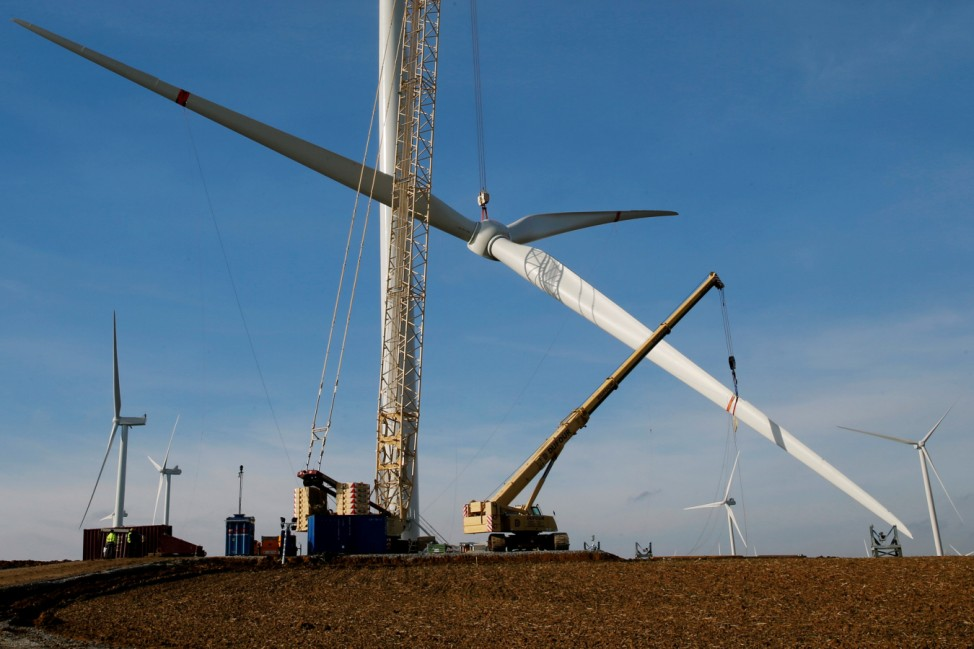 A crane lifts a propeller to the top of a power-generating windmill turbine in a wind farm in Graincourt-Les-Havrincourt