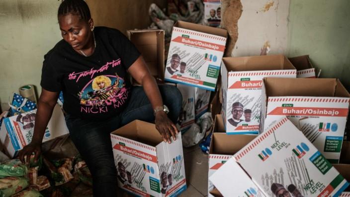 """Nigeria: """"Die meisten von uns haben ein Stipendium bekommen"""": Eine Frau packt Essenspakete für Unterstützer des amtierenden Präsidenten Buhari."""
