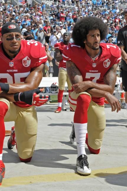 Football: Der Moment, als alles begann: Colin Kaepernick (re.), der Quarterback der San Francisco 49ers, kniet sich während der Nationalhymne aus Protest auf den Boden, einige Teamkollegen machen es ihm nach.
