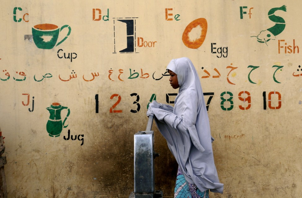 A girl draws water from a fountain a day after the postponement of the presidential election in Kano