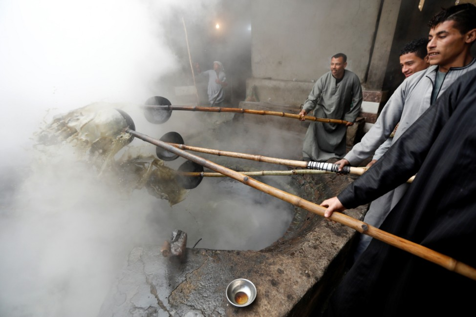 Workers cook 'black honey' molasses, made from sugar cane at a small factory in Mallawi