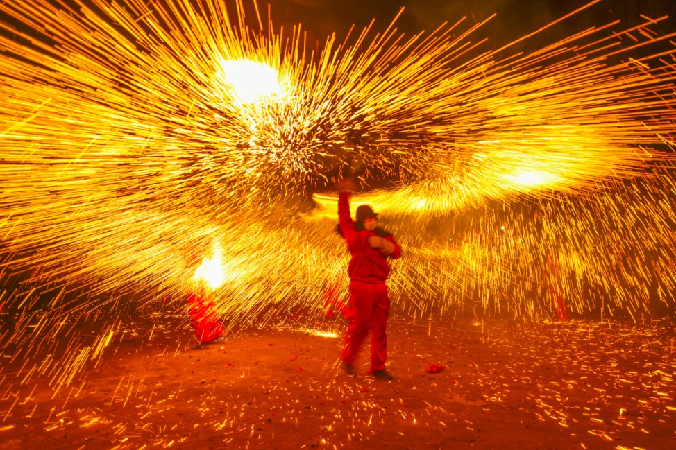 Folk artist makes a shower of sparks with molten iron during a local celebration ahead of the Chinese Lantern Festival, in Luzhou, Sichuan