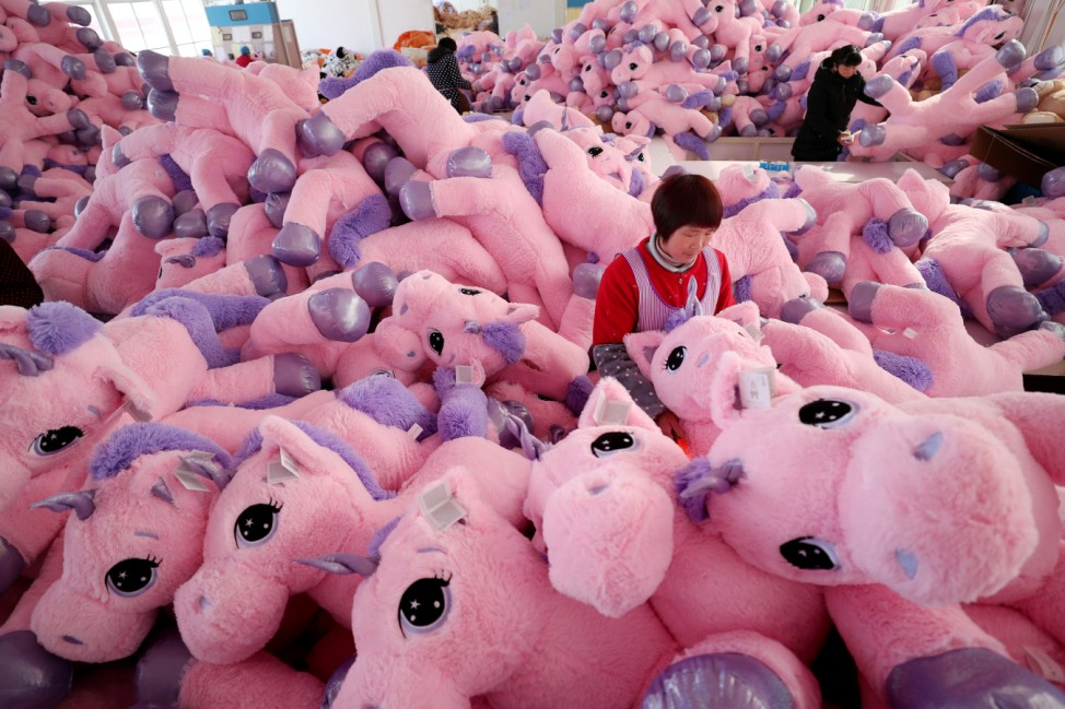 Women work on unicorn stuffed toys for export at a workshop in Lianyungang