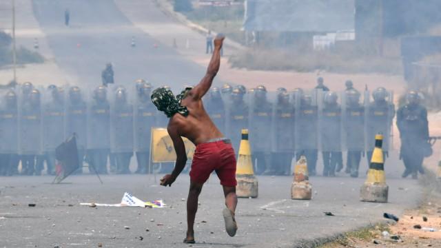 Venezuela - Ein Demonstrant wirft Steine in Richtung der Nationalgarde