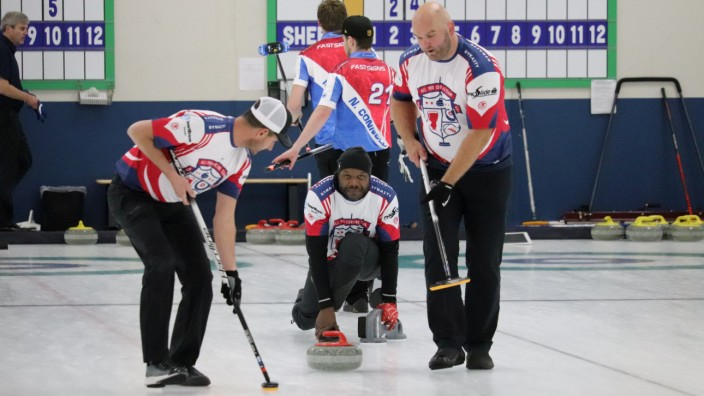 Former Tennessee Titans linebacker Bulluck throws a stone while teammates Bulger and Roos prepare to sweep during the USA Curling Men's Challenge Round in Blaine