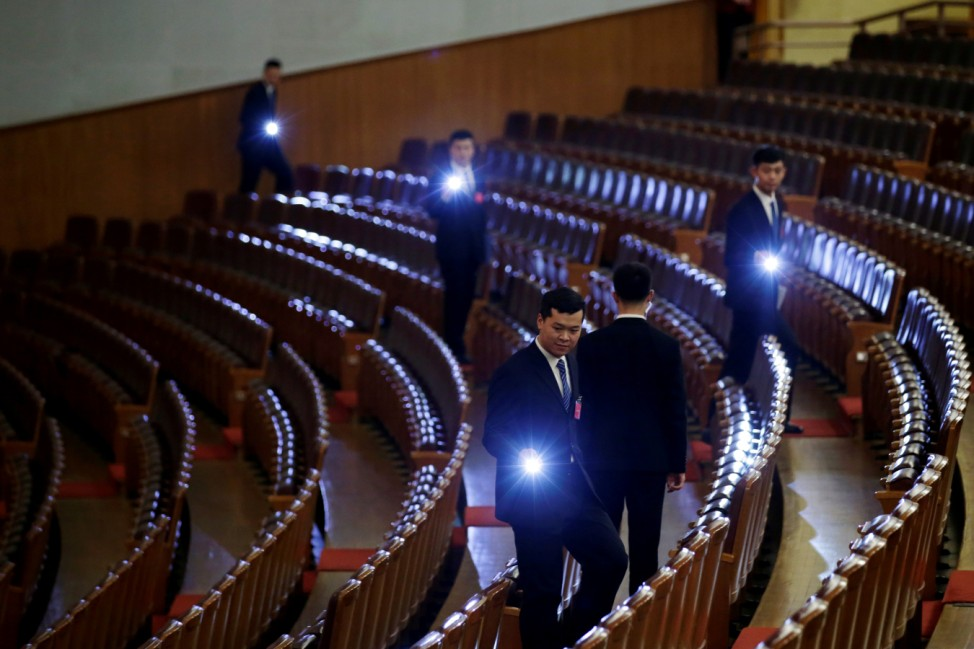 Security personnel check the seats with torches at the end of the opening session of the National People's Congress (NPC) at the Great Hall of the People in Beijing