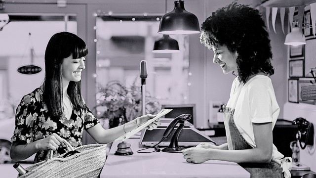 Smiling customer and shop assistant at counter of a store model released Symbolfoto property release