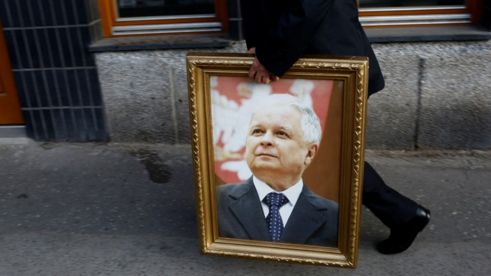A man holds picture of late President Kaczynski as he walks before a ceremony marking the seventh anniversary of the crash of the Polish government plane in Smolensk, Russia, that killed 96 people, in Warsaw