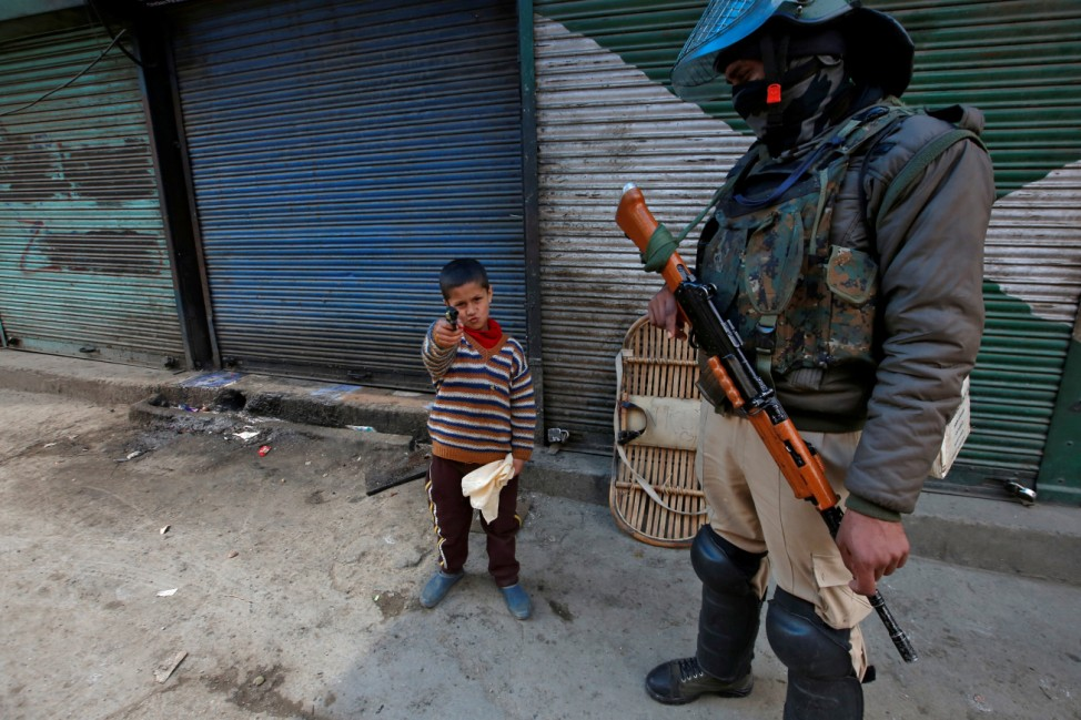 A boy plays with his toy pistol next to an Indian policeman standing guard in front of closed shops during a strike called by Kashmiri separatists against the arrest of Yasin Malik, in Srinagar