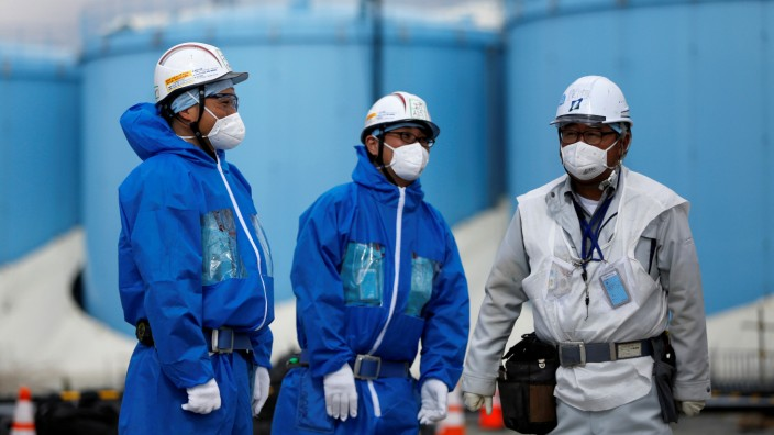 Workers are seen in front of storage tanks for radioactive water are seen at tsunami-crippled Fukushima Daiichi nuclear power plant in Okuma town, Fukushima prefecture