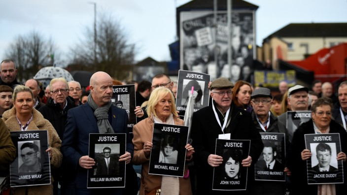 Families of the victims walk through the Bogside before the announcement of the decision whether to charge soldiers involved in the Bloody Sunday events, in Londonderry