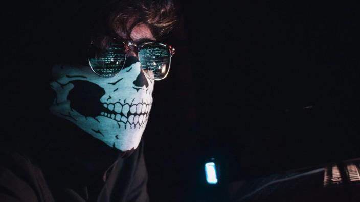 Mann mit Totenkopf-Maske vor Computerbildschirm
