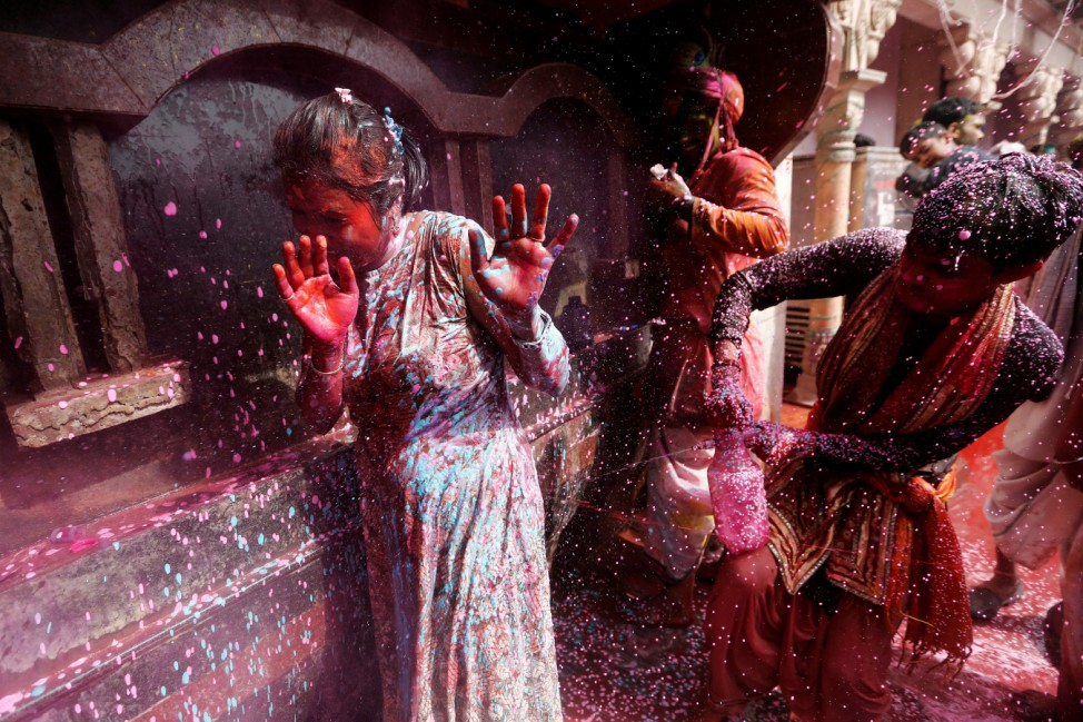 A boy sprays coloured water on a girl during religious religious festival of Holi inside a temple in Nandgaon