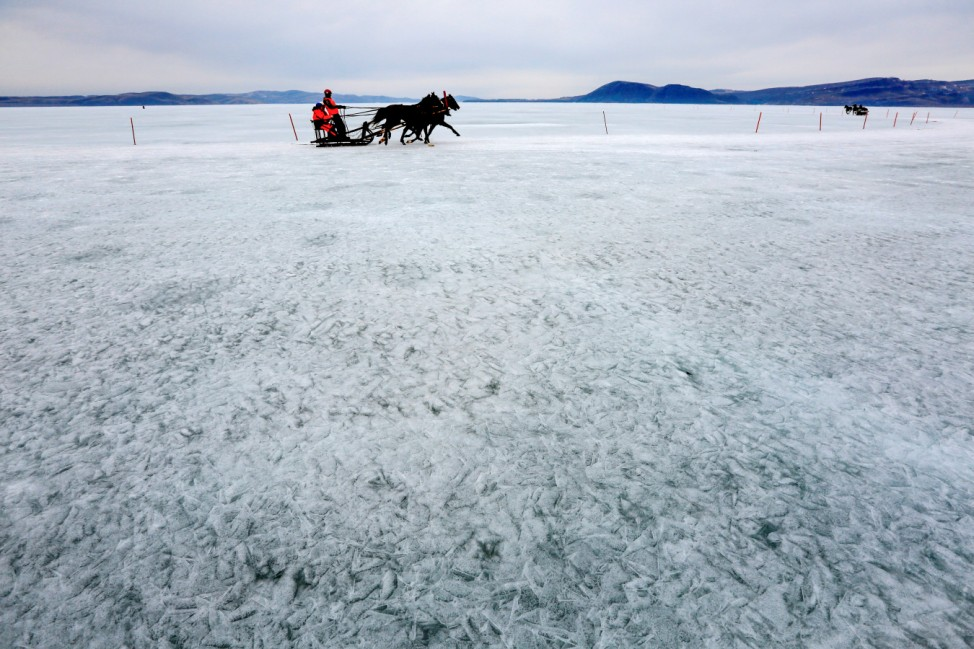 A Russian Troika, sledge drawn by three horses, competes on the ice-covered Yenisei River during the annual Ice Derby amateur horse race near the Siberian settlement of Novosyolovo, south of Krasnoyarsk