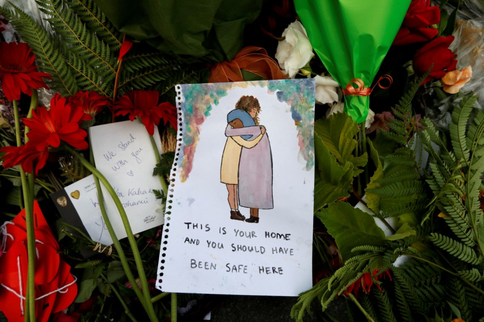 Flowers and signs are pictured at a memorial as a tribute to victims of the mosque attacks, near a police line outside Masjid Al Noor in Christchurch