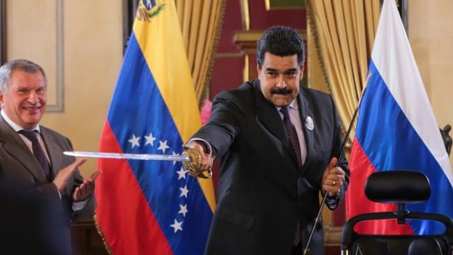 FILE PHOTO: Venezuela's President Maduro holds a replica of Venezuela's national hero Simon Bolivar's sword as Head of Rosneft Igor Sechin and Venezuela's Oil Minister and President of PDVSA Eulogio del Pino look on in Caracas