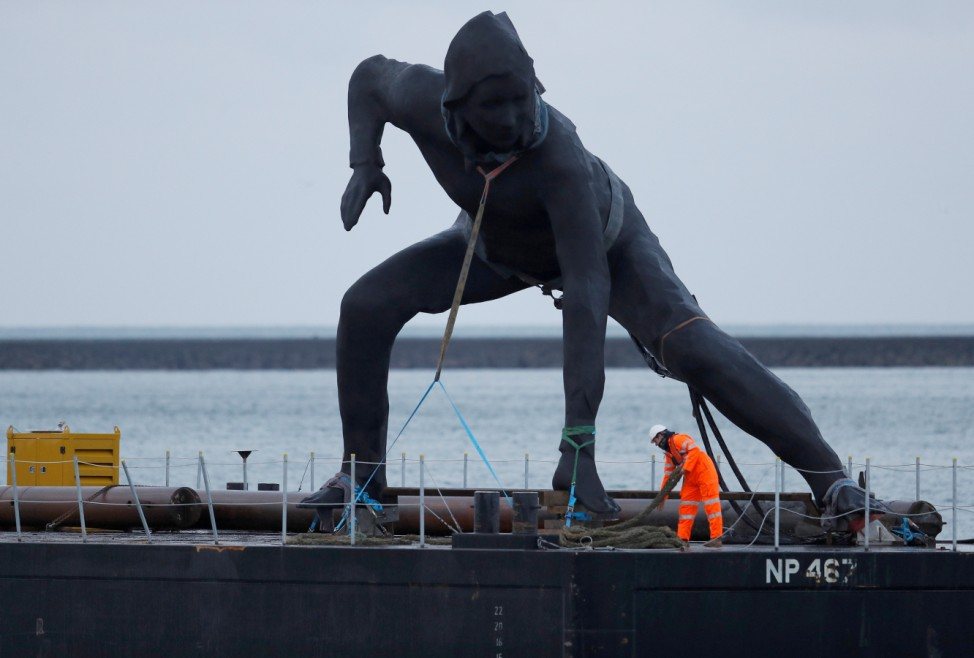 Britain's largest bronze sculpture, 'Messenger' arrives by barge in Plymouth Sound before being taken by road to the Theatre Royal in Plymouth