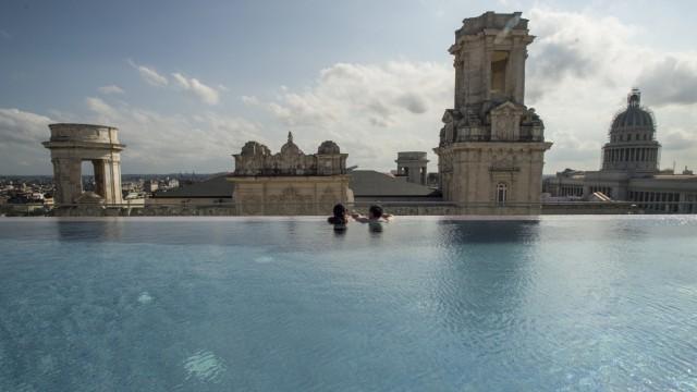 Ein junges Paar schaut vom Pool der Dachterrasse eines Luxushotels auf die Altstadt von Havanna.