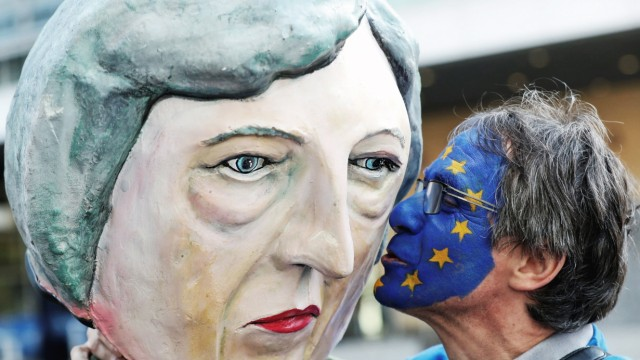 An anti-Brexit demonstrator kisses a protester dressed as Britain's Prime Minister Theresa May ahead of a EU Summit in Brussels
