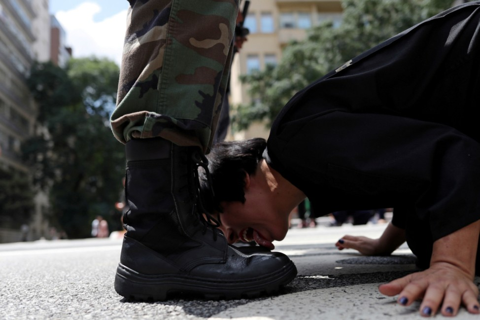 Venezuelan artist Deborah Castillo licks the boots of a man dressed as a member of the military during her performance 'Lamebrasil, Lamezuela - questioning power in Latin America,' in Sao Paulo
