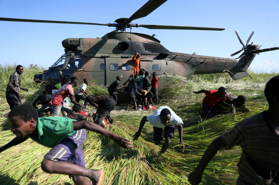 People run after collecting food aid from a South African National Defence Force (SANDF) helicopter in the aftermath of Cyclone Idai in Nhamatanda
