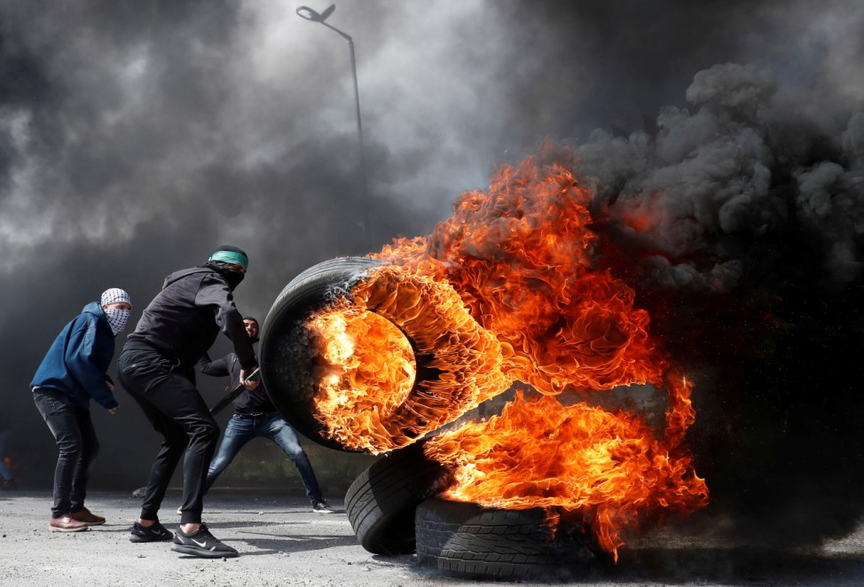 Palestinian protester moves a burning tire during clashes with Israeli troops in the Israeli-occupied West Bank
